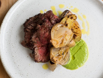 Barbecued bavette steak with green sauce, IPA-braised onions and barbecued potatoes