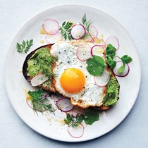 Fried eggs on toast with salted herb butter and radishes