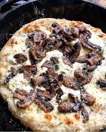 Frying pan pizza with garlic crème fraîche, mushrooms and Parmigiano Reggiano