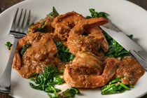 Shrimp cooked in Romesco with wilted spinach