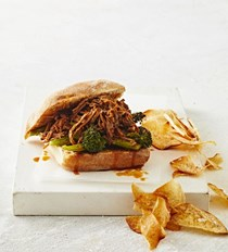 Slow-cooked pineapple pulled pork burger with roasted broccolini and taro chips