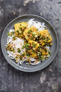 Turmeric-spiced fish with wilted herbs and peanuts