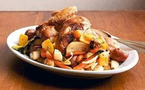 Whole roasted chicken on a bed of root vegetables